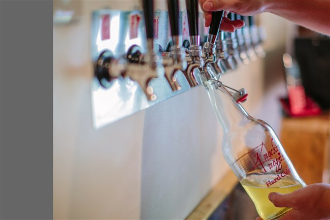 A growler of cider is filled at Knockin' Noggin Cidery & Winery in Volant, Pa.