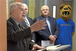 PSU President Eric Barron speaker during ceremonies at the Knead Community Cafe about the innovation and revitalization opportunities for the new small business co-working space called The Corner. In the background are Kevin Snider, chancellor of Penn State New Kensington, Mayor Thomas Guzzo, and the mascot of PSU the Nittany Lion.