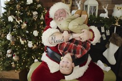 "Scott Diethorne, dressed as Santa, poses for a photo with at child upside down in his arms. Diethorne, the beloved Santa with ""naughty"" tattooed on one arm and ""nice"" tattooed on the other, has been asked to tone down his typically goofy poses at a suburban Philadelphia mall, leaving some fans miffed. Above, Diethorne holds a boy upside down, with permission from the boy's parents."