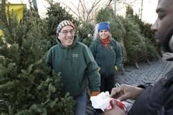 In this file photo, George Nash, left, and his wife, Jane Waterman, sell a tree to Kareem McGee outside Marcus Garvey Park in the Harlem neighborhood of New York on Dec. 7, 2017.