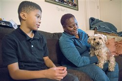 Keontay Copeland, 9, looks on as Tracy Copeland holds her dog, Snoopy, on her lap inside the family's McKees Rocks home.