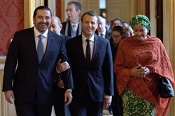 In this file photo, French President Emmanuel Macron (C) walks between Lebanon's Prime Minister Saad Hariri (L) and U.N. Deputy Secretary General Amina Mohammed (R) as they arrive to attend the Lebanon International Support Group meeting in Paris on December 8, 2017.