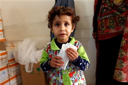 A Yemeni child suffering from malnutrition eats biscuits with nutritional supplements at a medical center on the outskirts of the Yemeni capital, Sanaa, on December 11, 2017.
