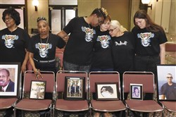 In this Feb. 10, 2017, file photo, family members of El Faro crew members stand with photographs of their loved ones during a break in a U.S. Coast Guard investigative hearing in Jacksonville, Fla.
