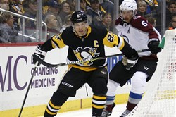 The Pittsburgh Penguins' Sidney Crosby works the puck behind the net with Colorado Avalanche's Erik Johnson defending in the second period of Monday's game in Pittsburgh.