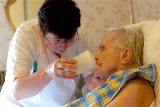 A nurse gives water to an elderly woman in a retirement home. An analysis shows that were you die can have a big impact on how you die.