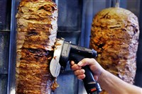 In this Nov. 30, 2017, file photo, a man slices cuts of meat from a rotisserie Doner spit inside a Doner restaurant cafe in Frankfurt, Germany.