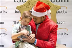 JuJu Smith-Schuster lets Jameson Marrow, 4, of Coraopolis, hold his dog Boujee King Schuster during an event held by Total Sports Enterprises at the Mall at Robinson Dec. 12. Fans paid to get their photo taken with JuJu, dressed as Santa Claus. The fundraiser benefited the Homeless Children's Education Fund.