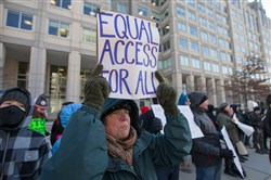"A woman holds an ""Equal Access For All"" protest sign during a demonstration against the proposed repeal of net neutrality outside the Federal Communications Commission headquarters in Washington on December 13, 2017."