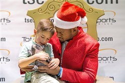 JuJu Smith-Schuster lets Jameson Marrow, 4, of Coraopolis, hold his dog Boujee King Schuster during an event Tuesday at the Mall at Robinson.