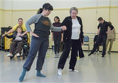 "With assistance from Jamie Murphy, left, of Pittsburgh Ballet Theatre School,  Betty Garland, 84, a resident of Lutheran SeniorLife  Passavant Retirement Community in Zelienople, practices basic ballet dance moves in mid December.at the ballet school in the Strip District. PBT offered the class ""Mindful Movement"", a program for individuals living with Alzheimer's Disease and their caretakers."