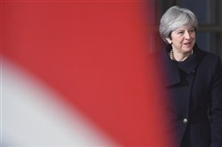 British Prime Minister Theresa May walks by the British flag during an EU summit at the Europa building in Brussels on Thursday, Dec. 14, 2017.