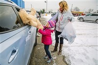 Emily Hughes, 5, hands a large teddy bear to a family in a car as her mother Jennifer watches during the Toys for Tots program on Friday in West Mifflin.