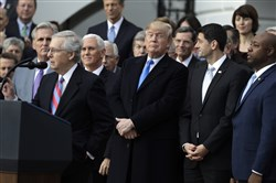 Senate Majority Leader Mitch McConnell speaks as President Donald Trump, House Speaker Paul Ryan and Sen. Tim Scott, R-S.C., right, listen during a tax cut bill passage event on the South Lawn of the White House last December.