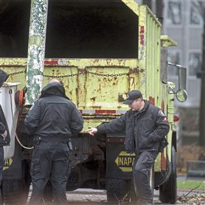 Pittsburgh Police officers investigate an industrial accident involving an Emery Tree Service tree-trimming truck on Saturday, Dec 23, 2017 in a courtyard between Gateway Towers the Condominium and One Gateway Center Downtown. City council voted to raise mandatory retirement to 70.