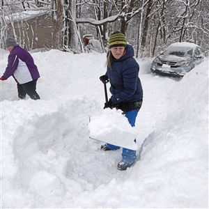 Fairview Township resident Natalie Latimer, 43, center, helps her niece Kristy Sheldon, 33, shovel her driveway on West Lake Road in Erie.