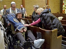 Sybil Epstein reaches out to touch the Torah as Sam Bernstein pushes Larry Buntman, carrying the Torah, around the congregation Saturday during the final Shabbat service at Temple Hadar Israel in New Castle Saturday.