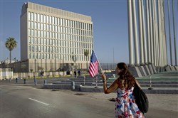In this July 20, 2015, file photo, American Elizabeth Fragoso holds a U.S. flag while walking toward the U.S. embassy in Havana, Cuba.