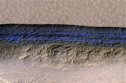 A cross-section of a thick sheet of underground ice is exposed at the steep slope that appears bright blue in this enhanced-color view from the High Resolution Imaging Science Experiment camera on NASA's Mars Reconnaissance Orbiter.