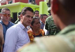 Mexican President Enrique Pena Nieto, left front, visits a zone affected by an earthquake in Oaxaca state, Mexico, on Sept. 8, 2017.
