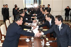 Members of the South Korea delegation (R) shake hands with members of the North Korean delegation (L) during their meeting at the border truce village of Panmunjom in the Demilitarized Zone dividing the two Koreas on January 9, 2018.