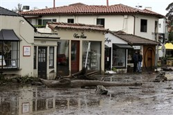 FILE - In this Tuesday, Jan. 9, 2018 file photo, debris and mud cover the street in front of local area shops after heavy rain brought flash flooding in Montecito, Calif. Mark Schniepp, director of the California Economic Forecast, said the area is being shaken by a three-pronged problem: Tourists aren't coming in their usual numbers, residents have been forced to move out and thousands of workers can't get to their jobs. (AP Photo/Daniel Dreifuss)