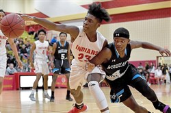 Penn Hills and Woodland Hills are dropping from Class 6A to 5A but will remain in the same section. Penn Hills' Myles Yarbough and Woodland Hills' Tre'mon Josey battle for the ball in a game earlier this season.