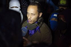 In this July 13, 2017, file photo, Oscar Perez speaks to the press at a night vigil to honor the more than 90 people killed during three months of anti-government protests in Caracas, Venezuela.