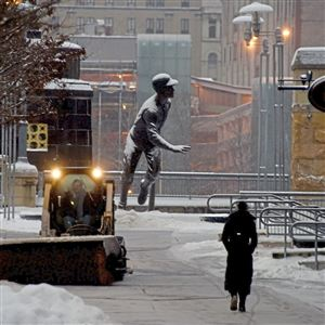 Workers clear snow from the sidewalk on Federal Street next to PNC Park on Tuesday. In the background, snow piles up on the Roberto Clemente statue.