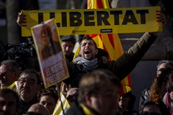 "A demonstrator holding a banner reading in Catalan ""Freedom"" gathers with others outside the Catalonia parliament during a parliamentary session in Barcelona, Spain, on Jan. 17, 2018."