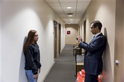 Hasan Shafiqullah, the director of the immigration unit at the Legal Aid Society of New York, takes Marcela Alcaide Eligio's photograph for her Deferred Action for Childhood Arrivals renewal application in New York on Jan. 16, 2018.