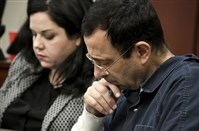 "A victim makes her ""impact statement"" to Larry Nassar during a sentencing hearing as he puts his head down in front of Judge Rosemarie Aquilina in district court on Tuesday, Jan. 16, 2018, in Lansing, Mich. Nassar has pleaded guilty to molesting females with his hands at his Michigan State University office, his home and a Lansing-area gymnastics club, often while their parents were in the room."
