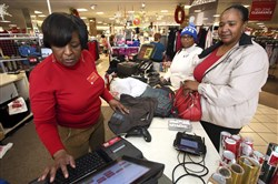 In this Dec. 26, 2017, file photo, J.C. Penney sales associate Wanda Cofield, left, assists Cynthia Putney, right, and Linda Pierce with returns and exchanges at the store at Golden East Crossing mall in Rocky Mount, N.C.