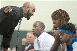 Westinghouse coach Eugene Wilson instructs James Ellis on the bench during a game against Allderdice this season.