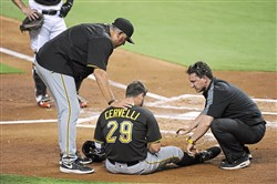 Francisco Cervelli sits on the ground and talks with head athletic trainer Todd Tomczyk and with Clint Hurdle after being hit by a pitch in the 2nd inning against the Miami Marlins at Marlins Park on June 2, 2016