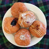 Paczki, a Polish filled doughnut, is a popular treat on Fat Tuesday,  the day of indulgence before the Christian fast known as Lent. The selections from Oakmont  Bakery in Oakmont include (clockwise from left) blueberry, apple, raspberry, maple bacon, and cookies and cream.