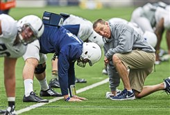 In this March 23, 2015, photo, Penn State athletic trainer Tim Bream talks with quarterback Christian Hackenberg as he stretches during an NCAA college spring football practice in State College, Pa.