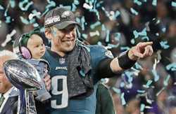 Philadelphia Eagles quarterback Nick Foles holds his daughter, Lily James, after winning the NFL Super Bowl LII against the New England Patriots Sunday night in Minneapolis.