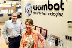 Wombat Security Technologies CEO Joe Ferrara, left, and Amy Baker, the vice president of marketing, stand inside the company Strip District offices in 2014.