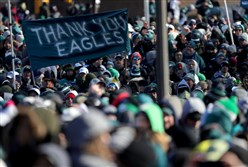 Fans hold up a sign thanking the Eagles at the Super Bowl celebration at the Art Museum in Philly Thursday.