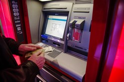 A customer withdraws money from an automatic teller machine inside a Bank of America branch in New York on Jan. 13, 2018.