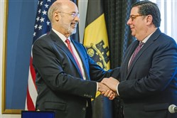 Pennsylvania Gov. Tom Wolf congratulates Mayor Bill Peduto after the announcement of the city's exit from Act 47 on Feb. 12, Downtown. The Act 47 status guided Pittsburgh back from the brink of bankruptcy.