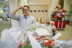 Parker Werns, a grad assistant for the Honors Program at Point Park University, sorts flowers for delivery on Valentine's Day.