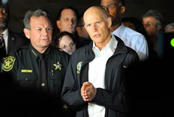 Republican Florida Gov. Rick Scott speaks to the media as he visits Marjory Stoneman Douglas High School following a shooting that killed 17 people on Feb. 14, 2018 in Parkland, Fla.
