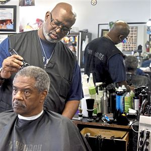 "Kevin ""Bat"" Andrews gives a haircut to George Gardner of Richland at Bat's Barber Shop along Penn Avenue in East Liberty. Mr. Andrews has had the shop in East Liberty for 15 years and is hoping to stay, but fears getting priced out by further rent increases in the key Penn-Highland corridor."