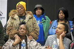 Joyce Daniels (seated left), mother of Mark Daniels, holds hands with family friend Elaine Haines (upper left), and Denise Jones (right) during a press conference at the Community Empowerment Association in Homewood on Friday. Mark Daniels  was shot and killed by police on Sunday.