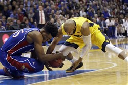 Kansas center Udoka Azubuike, left, and West Virginia guard Jevon Carter dive for a loose ball during the first half Saturday in Lawrence, Kan.