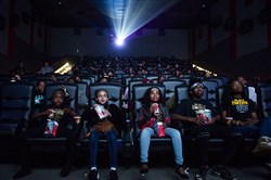 "Flint resident Mari Copeny, also known as Little Miss Flint, third from left, takes a sip of her soda as she watches a free screening of the film ""Black Panther"" with more than 150 Flint children after she raised $16,000 to provide free tickets in an entire theater Feb. 19, 2018, at Rave Cinemas Flint West 14 in Flint Township, Mich."