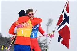 Norway's Simen Hegstad Krueger and Norway's Johannes Hoesflot Klaebo celebrate their gold win at the end of the men's 4x10kms classic freestyle cross country relay at the Alpensia cross country ski centre during the Pyeongchang 2018 Winter Olympic Games on February 18, 2018 in Pyeongchang.