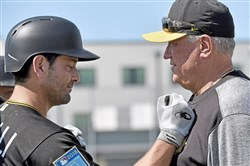 Pirates manager Clint Hurdle talks with catcher Francisco Cervelli during the team's first full-squad workout at Pirate City Feb. 19.